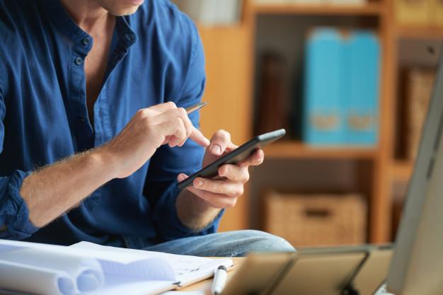 hombre-irreconocible-vestido-informalmente-usando-telefono-inteligente-trabajo-oficina-boli