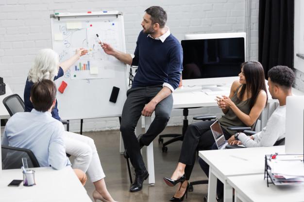 hombres-mujeres-trabajadores-oficina-debatiendo-sillas-pizarra-documentos-ordenador-mesas