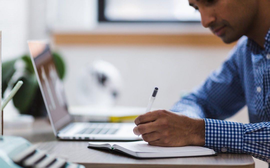 ordenador-portatil-mac-apple-mano-boligrafo-maquina-escribir-libreta-hombre-camisa-cuadros-azul-blanco